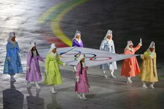 Former South Korean Olympians and Olympic gold medalists carry the Olympic flag into Olympic Stadium at the 2018 Winter Olympics Stock Image