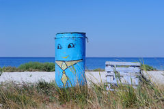 Former Water Tank and Beach. A painter water tank on a beach close to a wooden bench on the sea background stock images