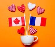 Formes blanches de tasse et de coeur avec des drapeaux de Frances et de Canada Photo libre de droits