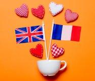 Formes blanches de tasse et de coeur avec des drapeaux de Frances et du Royaume-Uni Photographie stock libre de droits