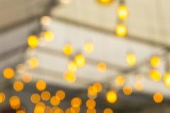 Formes brouillées des lampes électriques incandescentes placées sous le toit Images stock