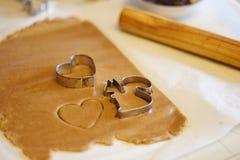 Formes de coupeur de quelques biscuits sur la pâte crue de biscuit, une avec la forme de coeur, un autre - écureuil Différentes f images libres de droits
