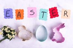 Formes de lièvres, d'oeuf et de poulet, fleurs, texte de Pâques photographie stock libre de droits