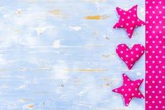 Formes roses de coeur et d'étoile sur le bois bleu-clair de vintage avec l'espace de copie Photo stock