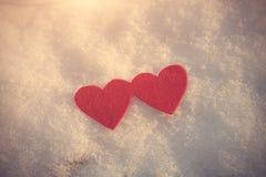Formes rouges de coeur sur la neige Images stock
