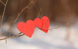 Formes rouges de coeur sur la neige Photos libres de droits