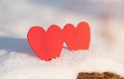 Formes rouges de coeur sur la neige Image stock