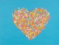 Formez du coeur présenté sur un fond bleu de petits chocolats Photos stock
