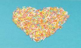 Formez du coeur présenté sur un fond bleu de petits chocolats Photo libre de droits