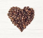 Formez le coeur des grains de café sur le fond en bois, Valent Images libres de droits
