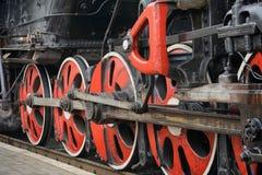 Formez le mécanisme d'entraînement et les roues rouges d'une vieille locomotive à vapeur Image libre de droits