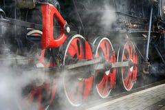 Formez le mécanisme d'entraînement et les roues rouges d'une vieille locomotive à vapeur Images libres de droits