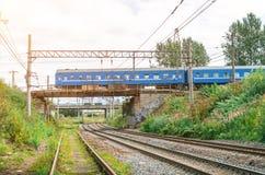 Formez les commandes d'une voiture de tourisme le long d'un pont en chemin de fer par un chemin de fer d'ami Photographie stock libre de droits
