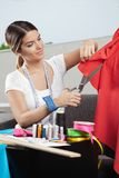 Formgivare Cutting Red Fabric fotografering för bildbyråer