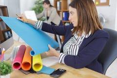 Formgivare som rullar ut och kontrollerar rullande papper för blått Royaltyfri Bild