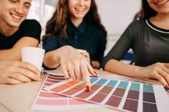 Formgivarearbete med färgprövkopior som dricker kaffe arkivbild