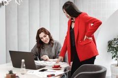 Formgivaren för två unga kvinnor arbetar på designprojektet av inre på skrivbordet med bärbara datorn och dokumentation i arkivbild