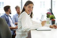 Formgivaren i tillfällig kläder är att sitta som ser kameran, och le, arbetar hans kollegor i bakgrunden arkivbild