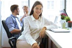 Formgivaren i tillfällig kläder är att sitta som ser kameran, och le, arbetar hans kollegor i bakgrunden arkivfoton