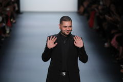 Formgivaren Michael Costello hälsar åhörarna på den Michael Costello modeshowen Arkivfoton