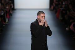 Formgivaren Michael Costello hälsar åhörarna på den Michael Costello modeshowen Arkivfoto