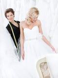 Formgivaren och bruden undersöker klänningen royaltyfria bilder