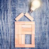 Formi della casa sopra l'albero su fondo di legno scuro e sulla lampadina del LED Imitazione del rame del riscaldamento o caldaia immagine stock
