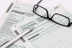 Formi di dichiarazione dei redditi con la penna ed i vetri Fotografia Stock