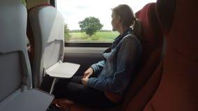 Formi la donna del passeggero sul viaggio che guarda fuori le colline verdi e gli alberi della finestra nel fondo - archivi video
