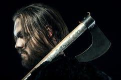 Formidabla viking i harnesk och yxa på svart bakgrund Royaltyfria Foton