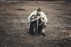 Formidable man with a sword in field sad. Royalty Free Stock Photography