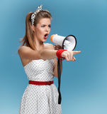 Formidable pin-up girl shouting into a megaphone, mouthpiece, speaking trumpet. Filmmaking or film production concept Stock Image