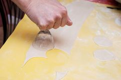 Forming blanks from a dough for home-made pelmeni by the hands royalty free stock photo