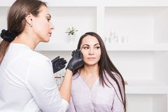 Beautician plucks a young woman`s eyebrows with tweezers royalty free stock photo