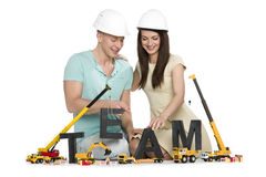 Forming a team: Cheerful man and woman building team-word. Royalty Free Stock Image