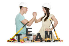 Forming a team: Joyful man and woman building team-word. Team building concept: Smiling young men and women building the word team along with construction Royalty Free Stock Images