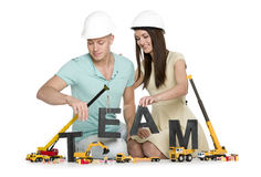 Forming a team: Joyous man and woman building team-word. Royalty Free Stock Photography