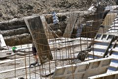 Placing forms and rebar to create a house foundation,. Forms are being set at basement level needed to create a foundation for a new house stock images