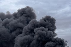 Forms and shapes in a cloud of toxic pollution smoke from a factory fire against a cloudy blue sky. stock images