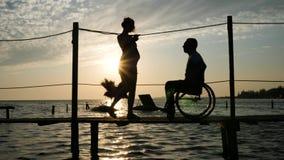 Formschöne Frau mit den Männern behindert auf dem Rollstuhl, der auf Anlegestelle am Damm gegen Himmel in der Nachglut geht stock footage