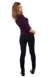 Formschöne junge Frau, die zurück der Kamera betrachtet Lizenzfreies Stockfoto
