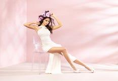 Formschönes Brunettemädchen, das auf dem Kristallstuhl sitzt Lizenzfreies Stockbild