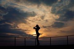 Formschönes Mädchen steht in den hohen Absätzen vor dem hellen Abendhimmel Stockbild