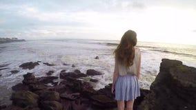 Formschönes und großes Mädchen steht auf einem Felsen auf der Küste des Ozeans auf der Insel Bali stock video