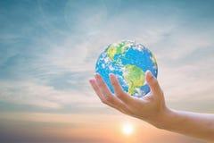 Formt die Welt auf menschlichen Händen, den Himmel im Hintergrund verwischt Umwelttagesökologiekonzept Überblick über dieses Bild Lizenzfreie Stockbilder