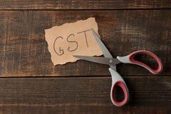 Formułuje GST z nożycami na brązu drewnianym tle na widok fotografia stock