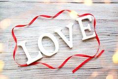 Formułuje miłości biali drewniani listy z czerwonym atłasowym faborkiem na białym drewnianym tle obrazy stock