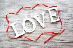 Formułuje miłości biali drewniani listy z czerwonym atłasowym faborkiem na białym drewnianym tle fotografia royalty free