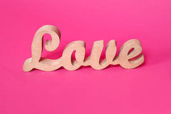 Formułuje miłości, drewniani listy na menchiach tapetuje Valentine& x27; s dnia tło Lovestory lub ślubny wystrój fotografia royalty free