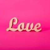 Formułuje miłości, drewniani listy na menchiach tapetuje Walentynki ` s dnia tło Lovestory lub ślubny wystrój Zdjęcie Stock